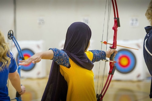 A youth practices target shooting with a bow during an educational archery event in Michigan. (Photo by Dave Kenyon, Michigan DNR.)