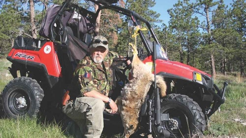 The author with a Black Hills coyote taken by way of Savage 6.5 Creedmoor while using high ground over long dry wash below. (Kill shot 397 ranged yards.)
