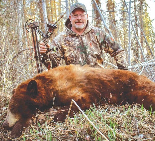 The author with his first cinnamon-colored black bear, which turned out to be the smaller of two color-phase bears hitting the same bait.