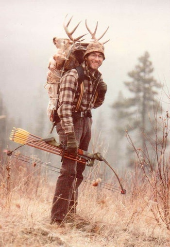 Dwight Schuh carrying one of the first compound bows on a successful deer hunt.