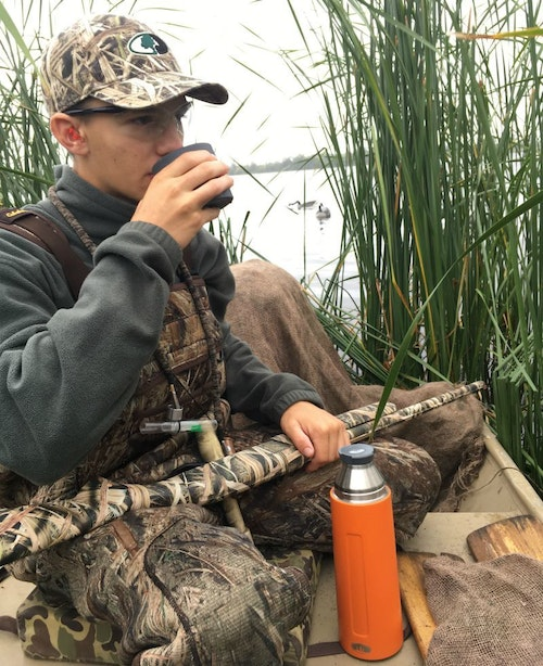When the shooting slowed, the author's son treated himself to hot chocolate in the duck blind.