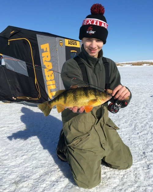The author's son, Elliott, steps out of the ice shelter to show off the duo's first camera fish.