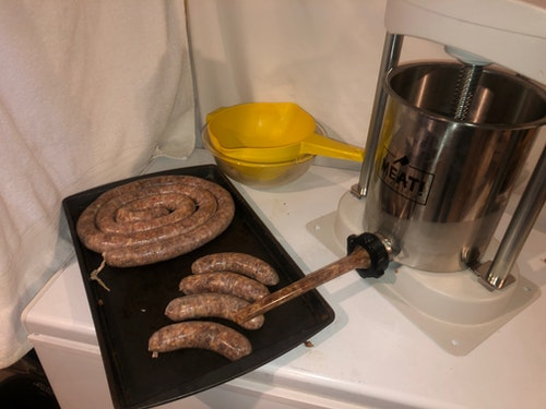Use a mechanical sausage stuffer to fill natural hog casings with the meat mixture.