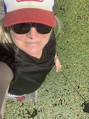 The author, standing on the railings of a dock (and taking a selfie), was casting a popper down into the openings and on the edges of a carpet of watershield. Photo: Amy Hatfield