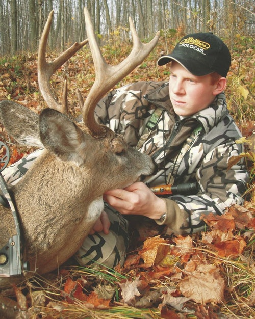 A teenager, the author admires his first buck from more than 15 years ago. He coaxed the buck within bow range via grunting, snort wheezing and rattling.