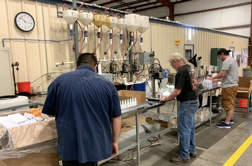 Pradco Fishing employees in the company's Fort Smith, Arkansas, facility making hand sanitizer for donation.