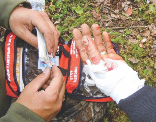 The author helps bandage the hand of an outfitter who cut himself during a skinning job in the backcountry.