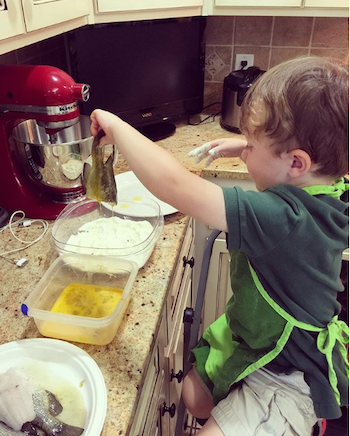 The author's son coats the bluegill in egg, then dredges each fish in cornmeal mix. Photo: Amy Hatfield