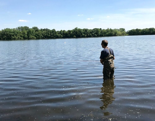 The author fly casting for spawning sunfish on a warm May afternoon. He wore breathable waders with jeans underneath to avoid overheating.