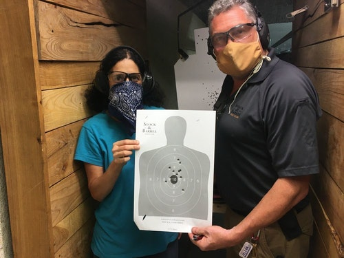 Claire and instructor David Williams, wearing masks because social distancing wasn't possible on the range, showing the target after firing her personal Glock 19.
