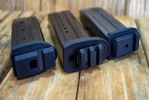 The left and right magazines show replacement baseplates for Sig Sauer P320 and P229 magazines. The center Smith & Wesson M&P magazine has a universal baseplate attached to the standard magazine.