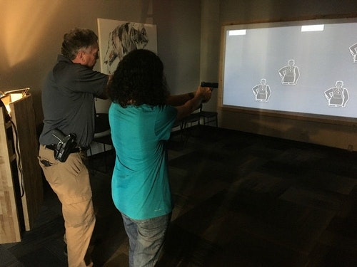 Claire learns how to properly aim a handgun in a virtual shooting range.