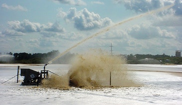 Lagoon aerator includes water cannon for foam suppression